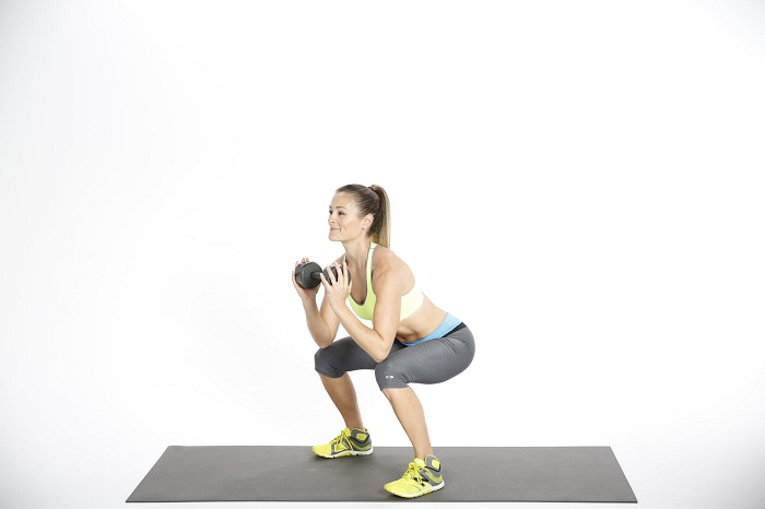 holding a dumbbell in both of your hands